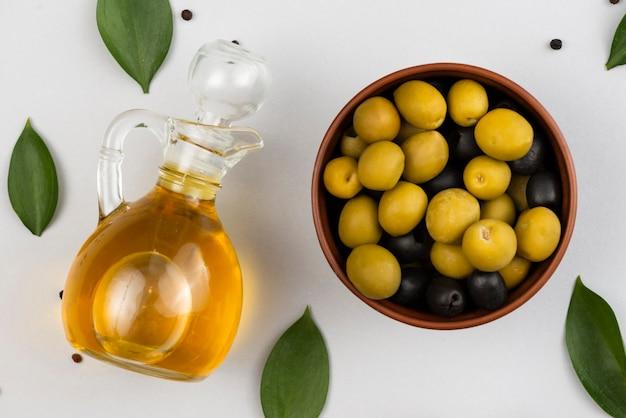Tigela com azeitonas e garrafa de óleo de azeitonas Foto gratuita