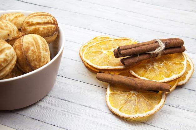 Tigela com biscoitos - nozes e fatias de laranja com canela, sobre um fundo claro de madeira Foto Premium