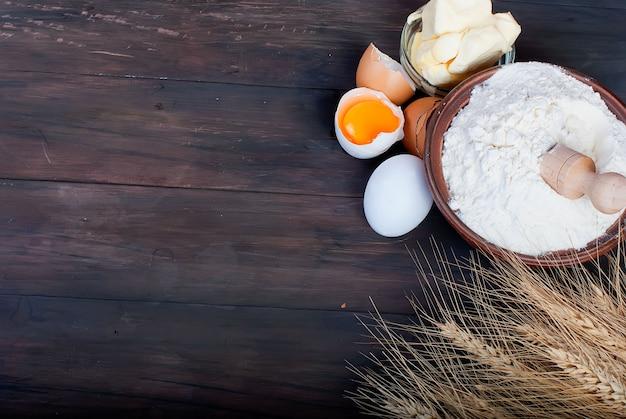 Tigela com farinha ovos espigas de trigo e manteiga no conceito de comida e bebida de tábua de madeira vintage Foto Premium