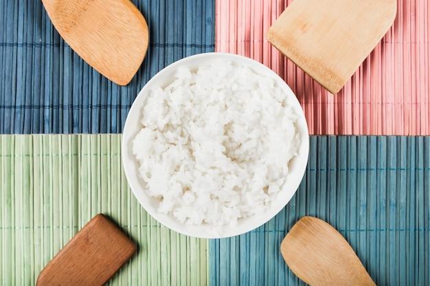 Tigela de arroz branco cozido no vapor com diferentes tipos de espátula de madeira no colorido placemat Foto gratuita