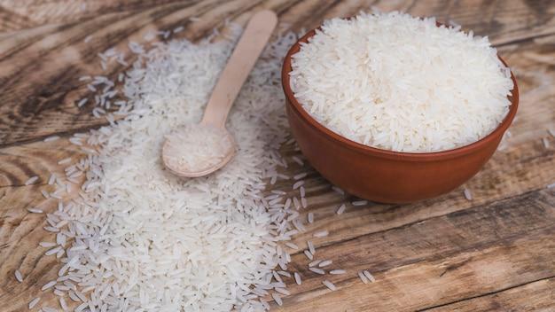 Tigela de arroz branco orgânico e colher de pau sobre o pano de fundo texturizado Foto gratuita