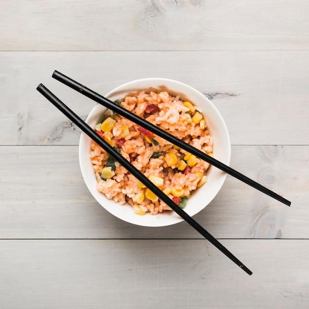 Tigela de arroz frito chinês com pauzinhos pretos na mesa de madeira Foto gratuita