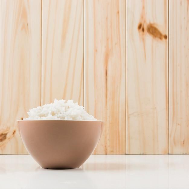 Tigela de arroz no chão em frente a parede de madeira Foto gratuita
