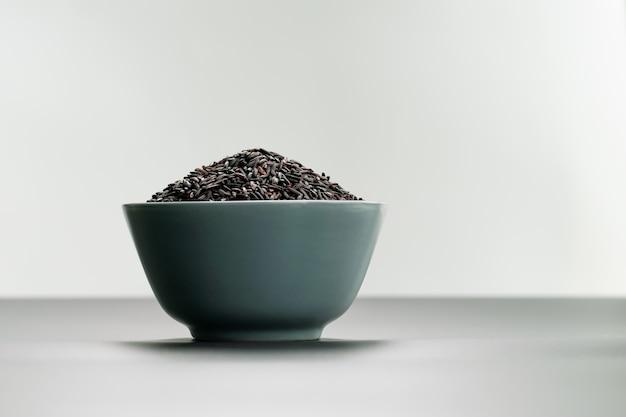 Tigela de arroz preto jasmim em fundos brancos Foto Premium