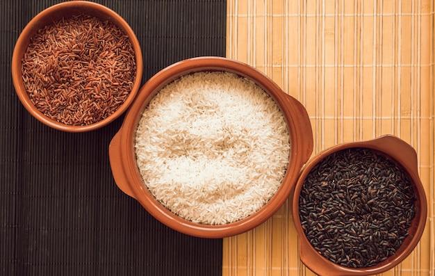 Tigela de arroz vermelho jasmim; arroz branco e tigelas de arroz preto no lugar Foto gratuita