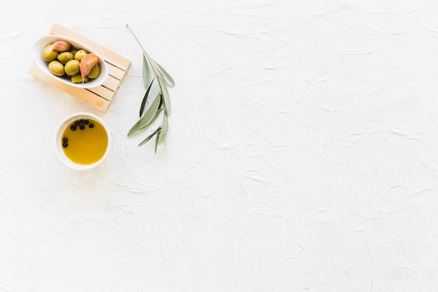 Tigela de azeite com óleo de pimenta preta e galho Foto gratuita