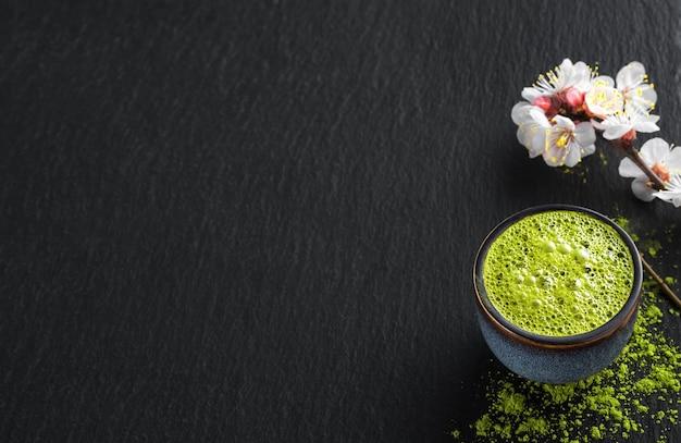 Tigela de azul com chá verde matcha, ao lado de um galho de cereja em flor e chá em pó na mesa Foto gratuita