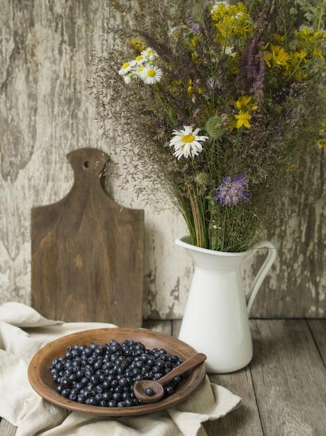 Tigela de barro com mirtilos e um jarro com flores silvestres em uma velha mesa de madeira. Foto Premium
