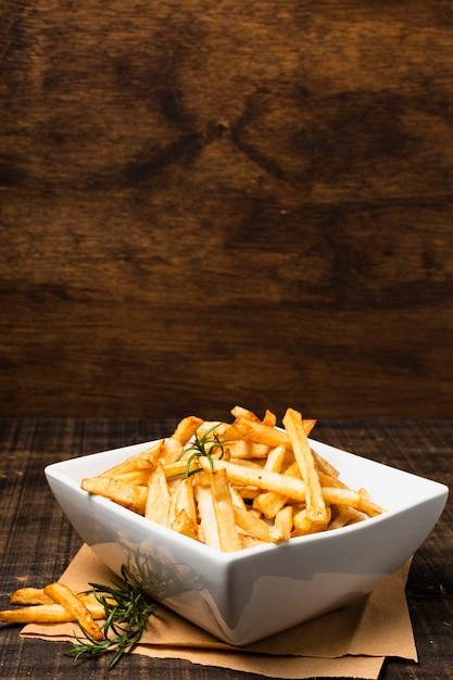 Tigela de batatas fritas na mesa de madeira Foto gratuita