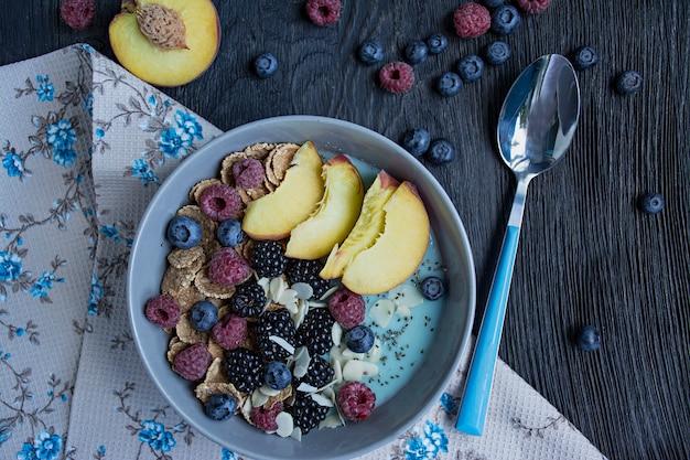 Tigela de batido com frutas frescas, sementes de chia, frutas e amêndoas. um conjunto de bagas framboesa, pêssego, mirtilos. café da manhã saudável. Foto Premium