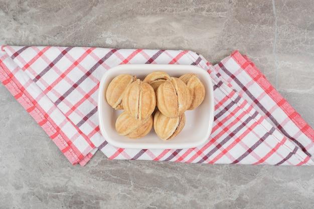 Tigela de biscoitos em forma de noz na toalha de mesa. Foto gratuita
