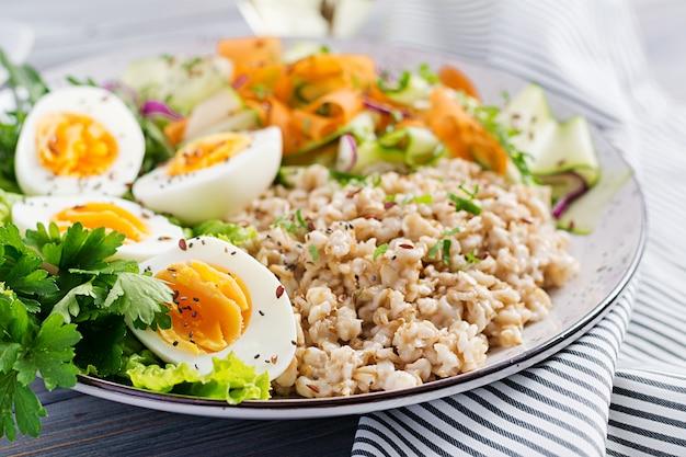Tigela de café da manhã com aveia, abobrinha, alface, cenoura e ovo cozido Foto gratuita