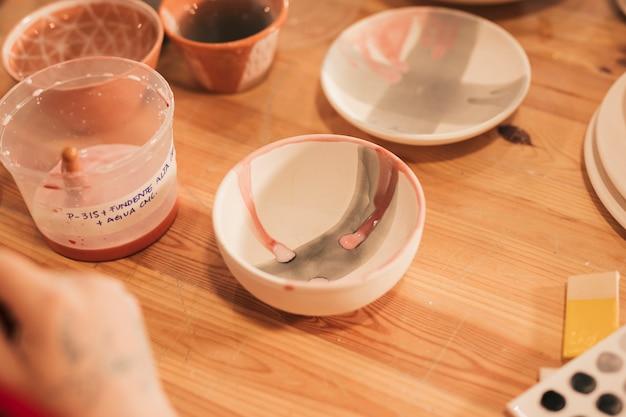 Tigela de cerâmica pintada e placa na mesa de madeira Foto gratuita