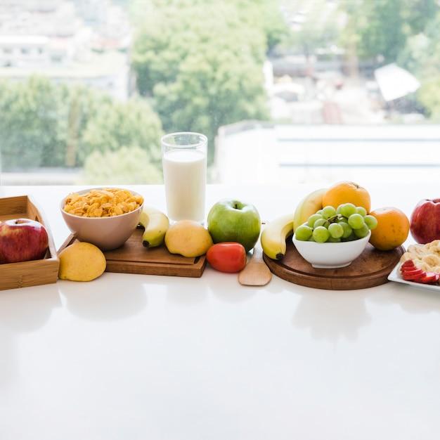 Tigela de cereais e frutas coloridas com copo de leite na mesa branca perto da janela Foto gratuita
