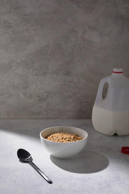 Tigela de cereal perto de um galão de leite em uma mesa branca perto de uma parede branca Foto gratuita