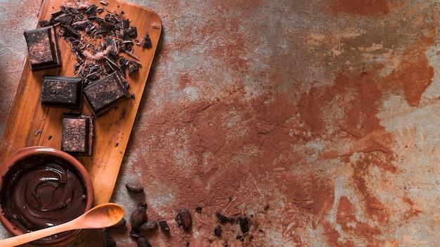Tigela de chocolate derretida e barra esmagada na tábua com colher de pau Foto Premium