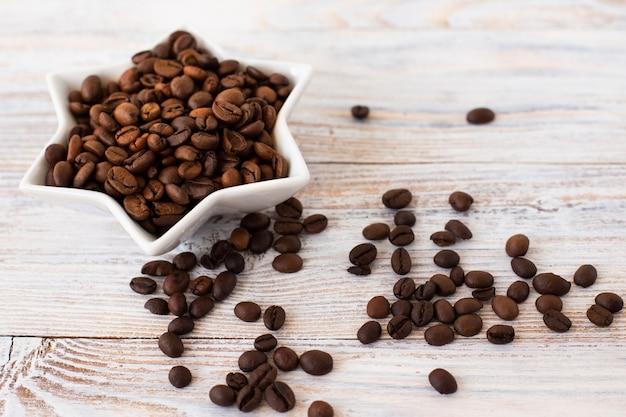 Tigela de close-up cheia de grãos de café Foto gratuita