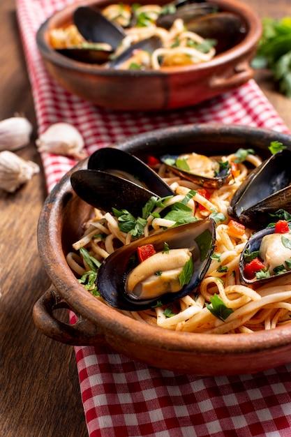 Tigela de close-up com deliciosas massas e mexilhões Foto gratuita