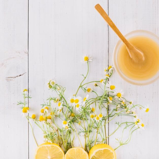 Tigela de coalhada de limão; flores de camomila e limão na prancha de madeira Foto gratuita