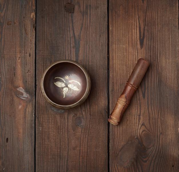 Tigela de cobre tibetana e vara de madeira sobre uma mesa de tábuas marrons Foto Premium