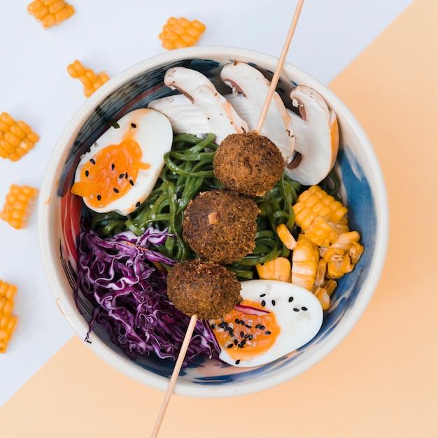 Tigela de comida asiática com ovo; macarrão; cogumelos; algas marinhas; repolho; milho e metade de ovos na tigela Foto gratuita