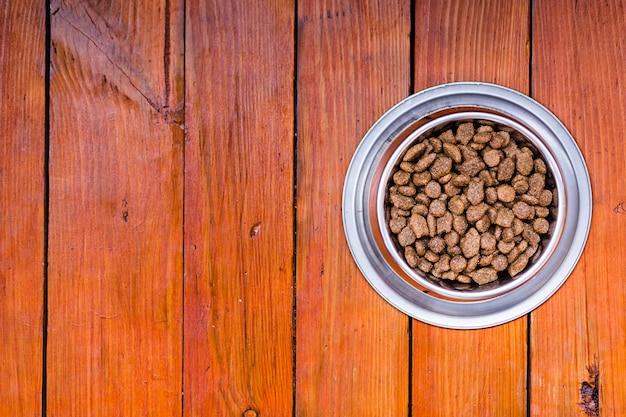 Tigela de comida para cães em fundo de madeira com espaço de cópia Foto gratuita