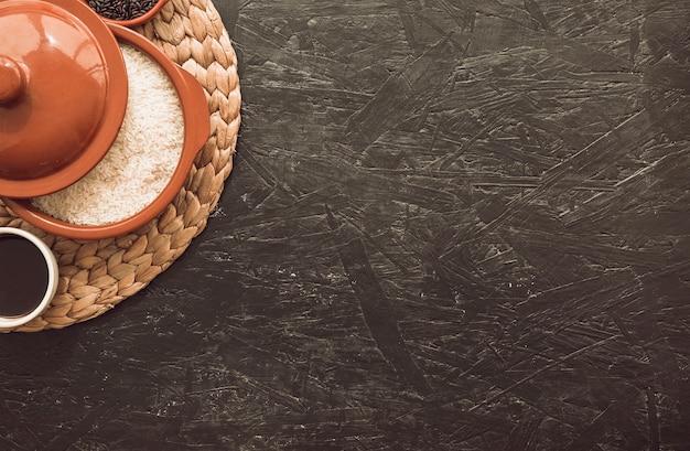 Tigela de grãos de arroz cru no placemat sobre o plano de fundo texturizado áspero Foto gratuita