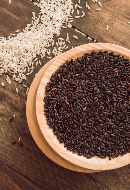 Tigela de grãos de arroz orgânico marrom com arroz branco na mesa Foto gratuita