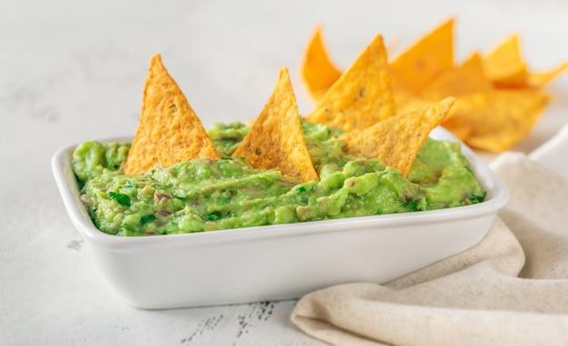 Tigela de guacamole com chips de tortilha na mesa Foto Premium