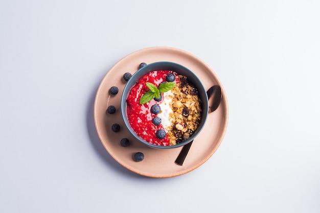 Tigela de iogurte com framboesas e granola Foto Premium
