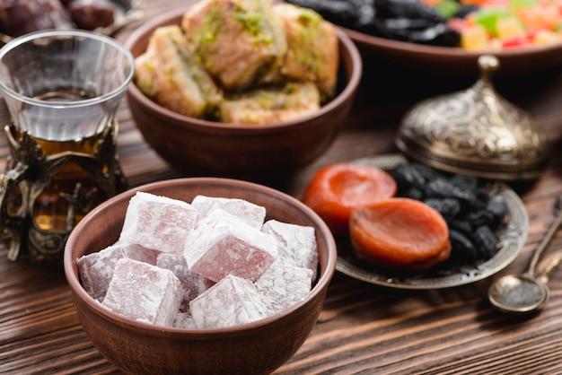 Tigela de lukum; chá e frutas secas na mesa Foto gratuita