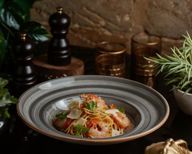 Tigela de macarrão com frutos do mar, verde basílico e parmesão Foto gratuita