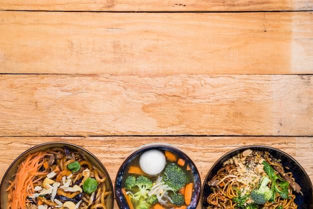Tigela de macarrão com sopa de bola de peixe na mesa de madeira com espaço de cópia Foto gratuita