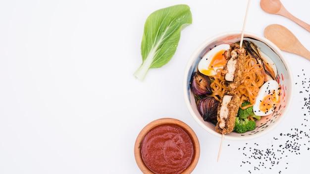 Tigela de macarrão udon com ovos; brócolis; sementes de gergelim e cebola no fundo branco Foto gratuita