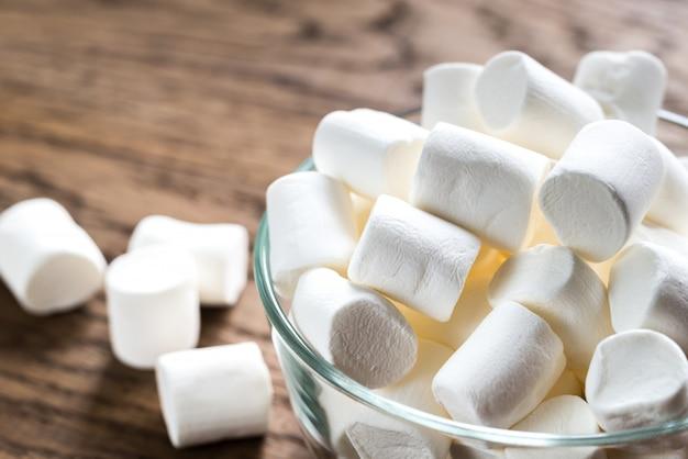Tigela de marshmallows na superfície de madeira Foto Premium
