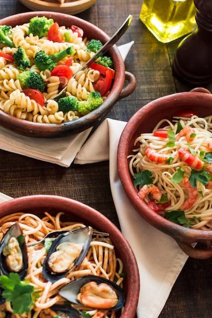 Tigela de massa vegetariana e não vegetariana na mesa de madeira Foto gratuita