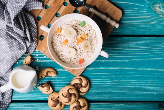 Tigela de mingau de aveia com coberturas de frutas e biscoitos Foto gratuita