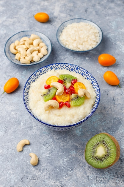 Tigela de mingau de flocos de arroz com fatias de kiwi, sementes de romã, cumquats e castanha de caju, vista superior Foto gratuita