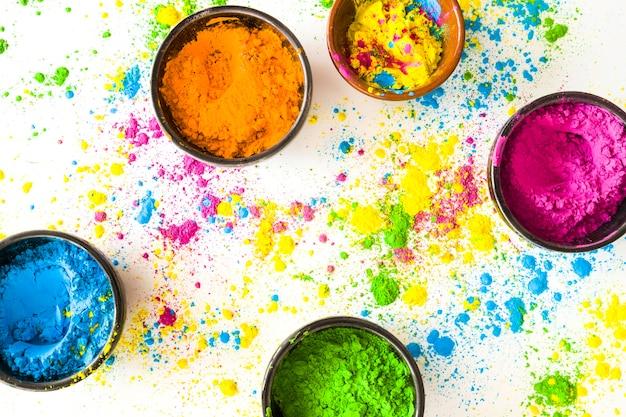 Tigela de pó colorido holi em fundo branco Foto gratuita