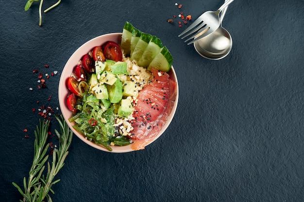 Tigela de puxão asiático com salmão, abacate, tomate cereja, pepino e wakame em uma tabela preta. comida saborosa e dieta. vista superior e fla lay com espaço de cópia Foto Premium