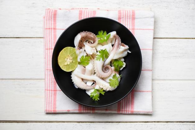 Tigela de salada de lula com ervas de limão e especiarias na superfície de madeira Foto Premium