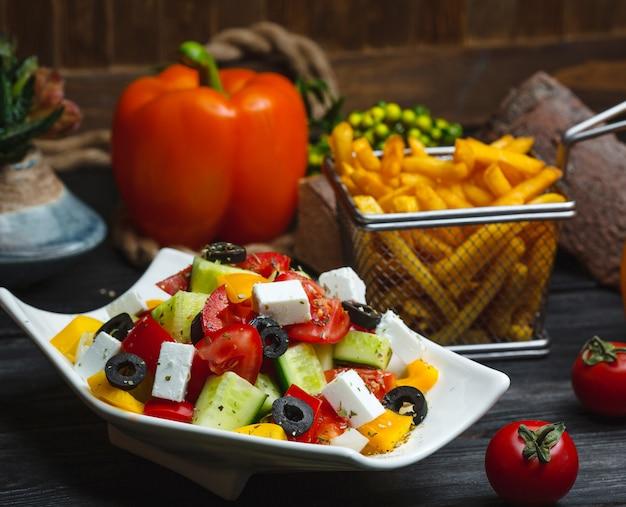 Tigela de salada grega, guarnecida com pimentão amarelo, servido com batatas fritas Foto gratuita