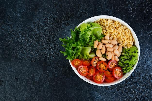 Tigela de salada vegetariana em um fundo preto de concreto em um prato. salada de bulgur e legumes frescos. o conceito de alimentação limpa e alimentação saudável. foto horizontal com espaço de cópia. vista do topo Foto Premium