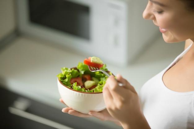 Tigela de salada verde fresca segurando em mãos femininas Foto gratuita