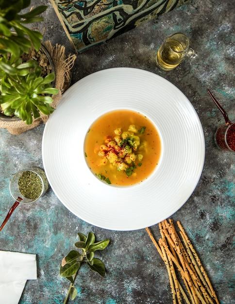 Tigela de sopa de abóbora com bolachas Foto gratuita
