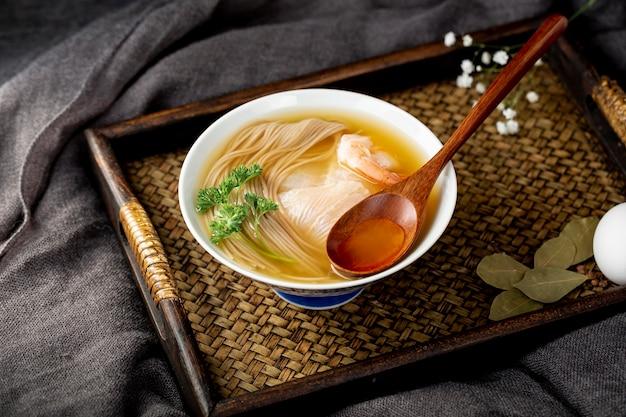 Tigela de sopa de macarrão com uma colher de pau em uma mesa de madeira Foto gratuita