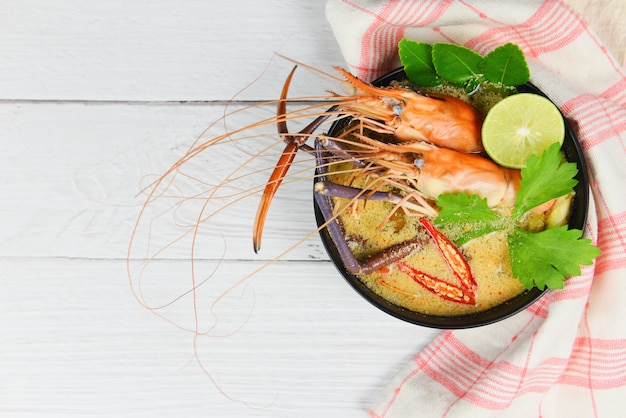 Tigela de sopa picante de camarão / frutos do mar cozidos com mesa de jantar de sopa de camarão e ingredientes asiáticos comida tailandesa tradicional, tom yum kung Foto Premium