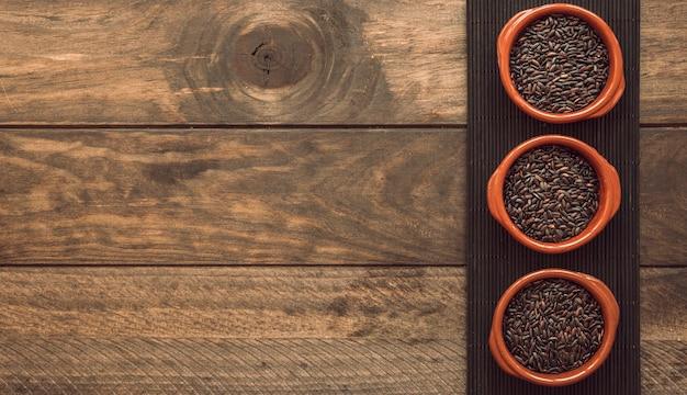 Tigela de três tigelas com arroz integral na bandeja sobre a mesa de madeira Foto gratuita