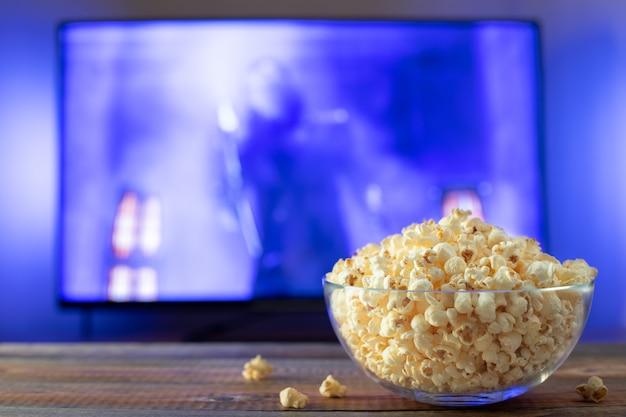 Tigela de vidro com pipoca e trabalhando tv. Foto Premium