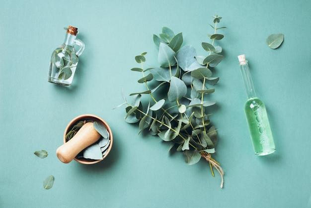 Tigela, frascos de óleo essencial de eucalipto, argamassa, ramo de ramos de eucalipto frescos Foto Premium